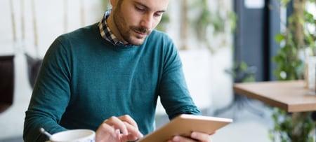 Man in sweater using iPad